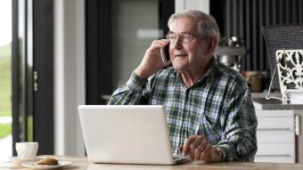 Senior male talking on smartphone while seated at table