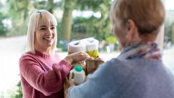 Neighbor Helping Senior Woman With Shopping