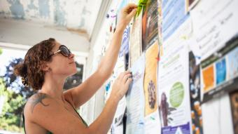 woman pinning up notice on community notice board