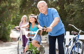 helping granddaughter ride bicycle