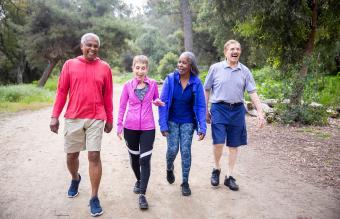 senior friends walking along a forest trail