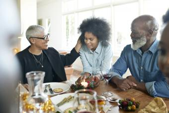 Teenage girl talking with family at dining table