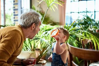 Grandson studying grandfather's face through magnifying glass