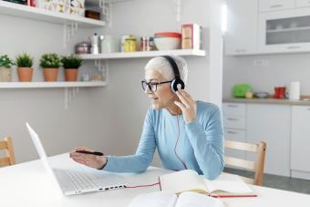 Senior Woman Learning Online With Headphones and Laptop at Home