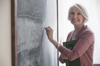 Senior woman writing on chalkboard