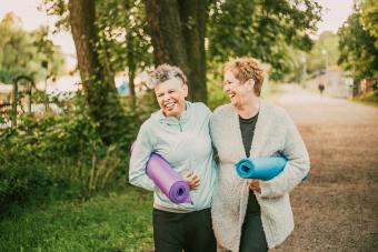 friends holding exercise mat while walking