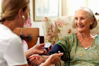 Caretaker measuring pressure largest assisted living companies