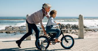 grandma teaching granddaughter to ride a bike at the beach