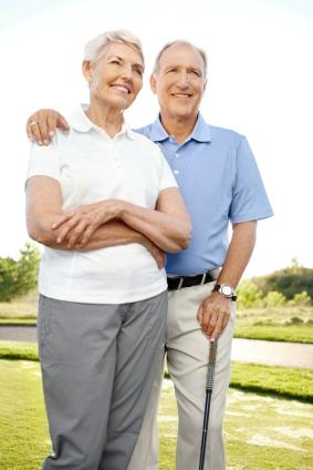 Happy retired couple golfing