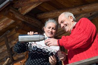 Senior couple standing on balcony of log cabin