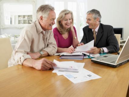 Couple With Financial Advisor At Table