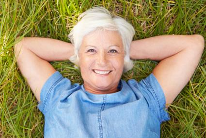 Senior woman lying on grass relaxing