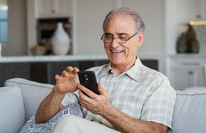 Senior man texting on cell phone