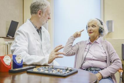 Senior patient wearing headphones and talking to audiologist