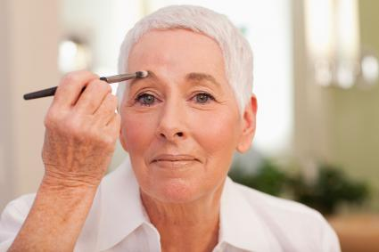 Senior woman putting on makeup