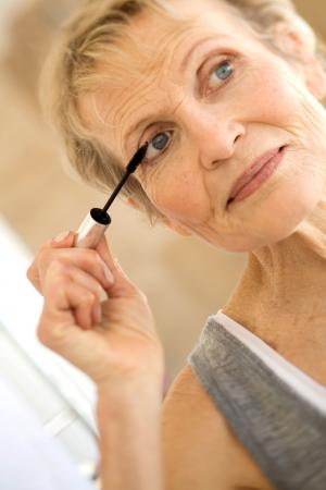 Woman applying mascara primer to lashes