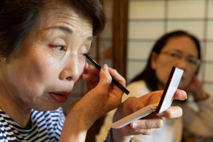 Senior woman putting on eye makeup