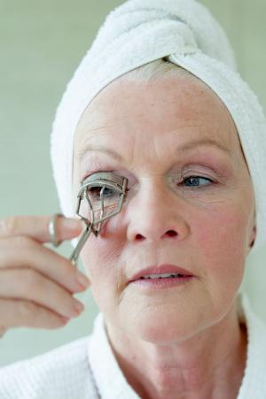 Senior woman using eyelash curler