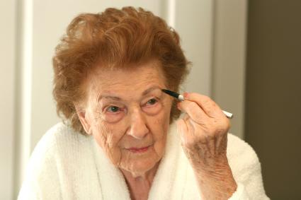 Senior woman using eyebrow pencil