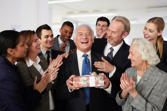 Colleagues giving retirement gift to businessman