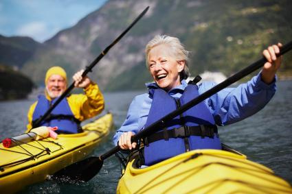 Senior couple kayaking on lake