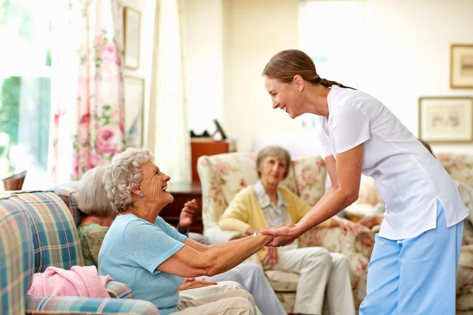 Nurse holding senior woman's hand