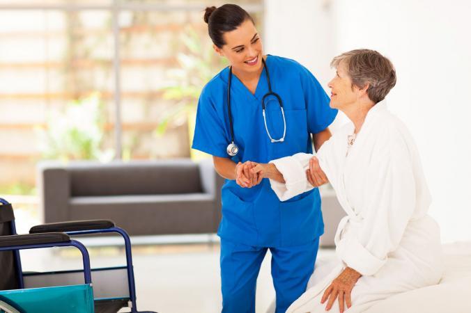 Nurse Helping Senior Woman into wheelchair