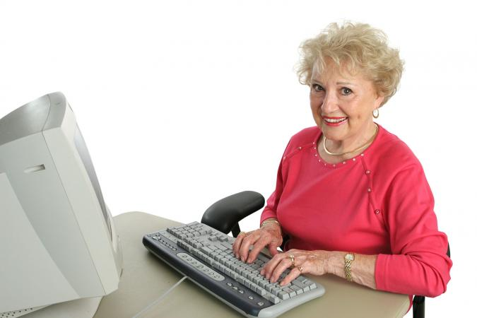 Senior woman typing on keyboard