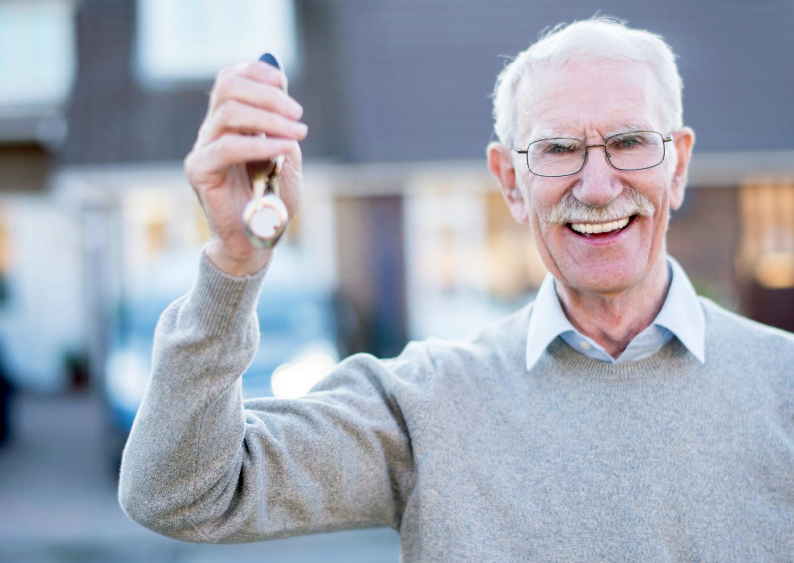 Senior man holding keys to his house