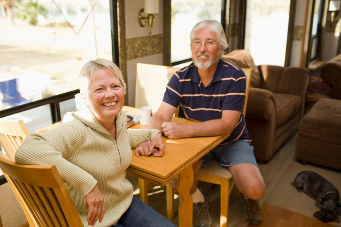 smiling senior couple sitting in motorhome