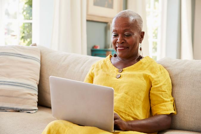 Senior woman on sofa using laptop