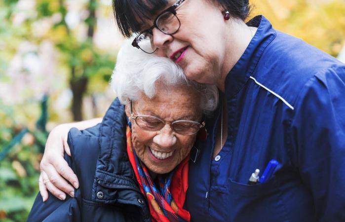 Caretaker embracing senior woman