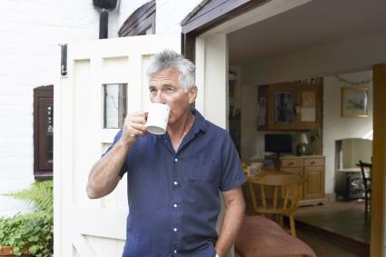 Mature man drinking tea in the doorway of his house