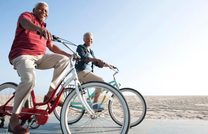 Couple riding bicycles by beach