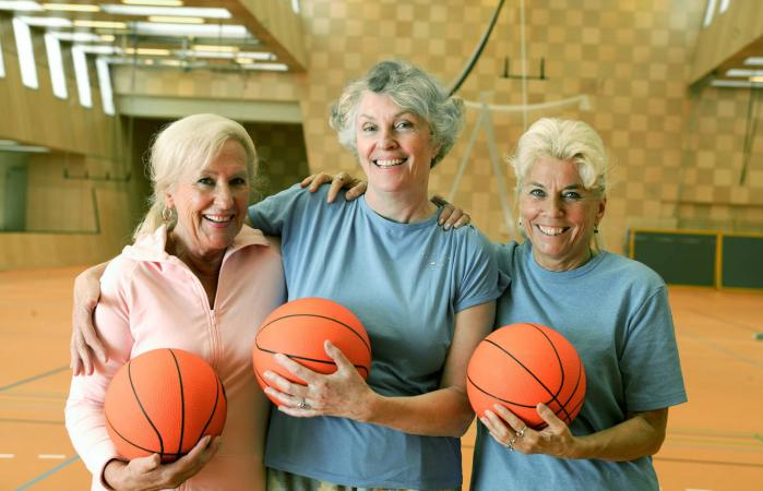 Senior women holding basketballs