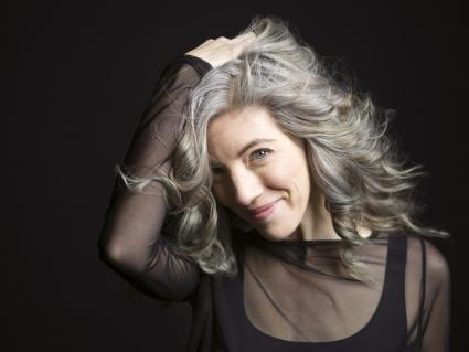 Confident woman with hand in gray hair