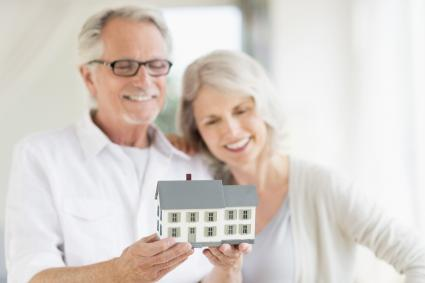 Senior couple holding a model home in their hands