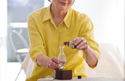 Senior woman using essential oil diffuser