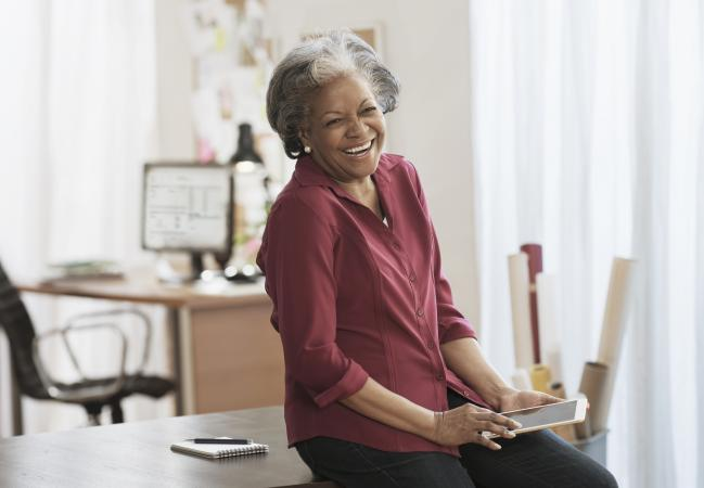 Senior woman laughing at tablet