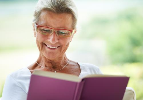 senior woman laughing at book