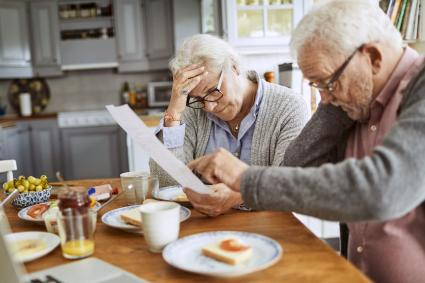 Senior couple having breakfast and doing bills
