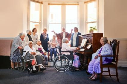 Group of senior women singing together and playing the piano at a retirement home