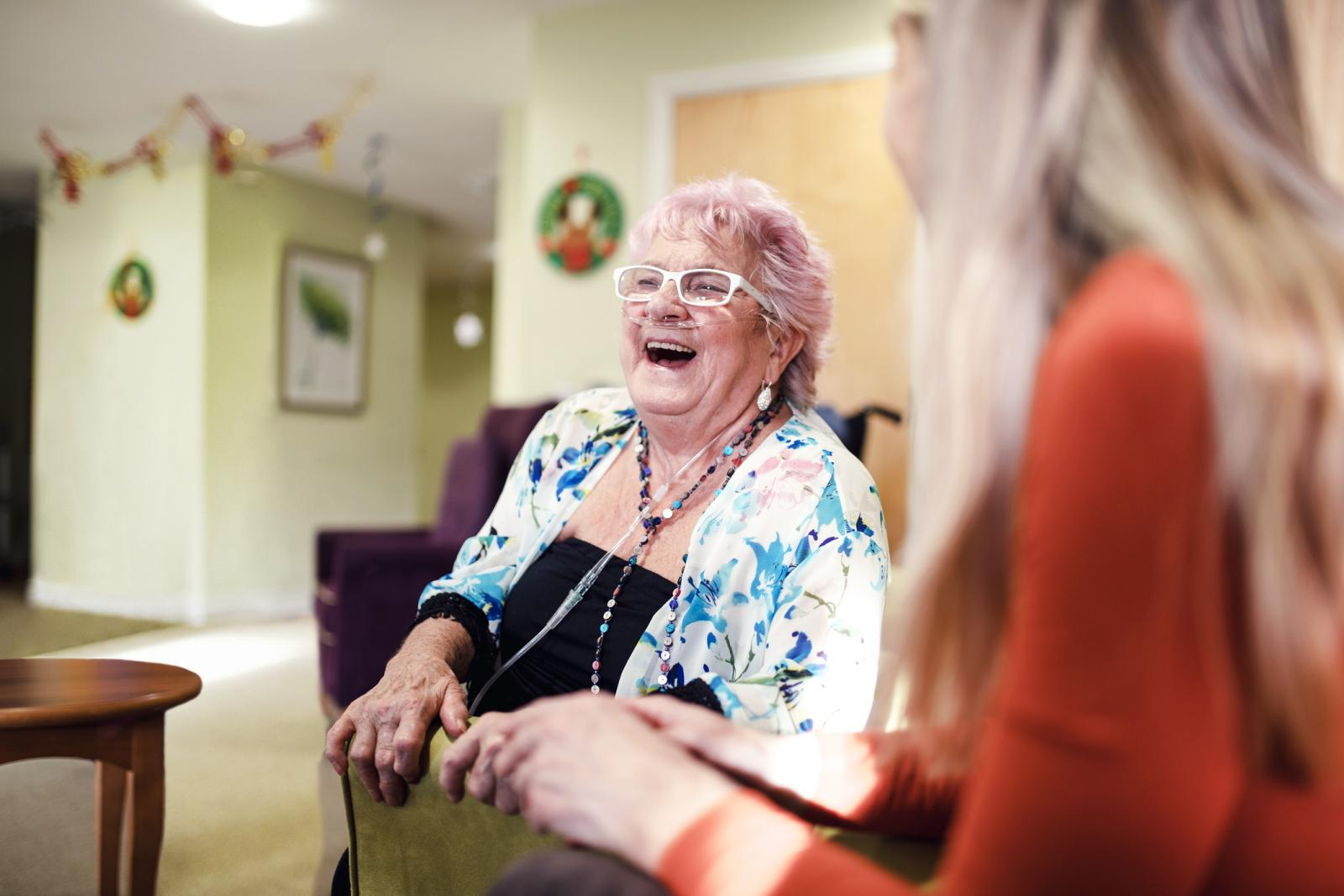 Senior woman talking to a younger woman who is visiting her in the care home