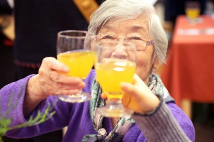 Senior Asian Woman Raising Glass of Non-Alcoholic Punch for Toast