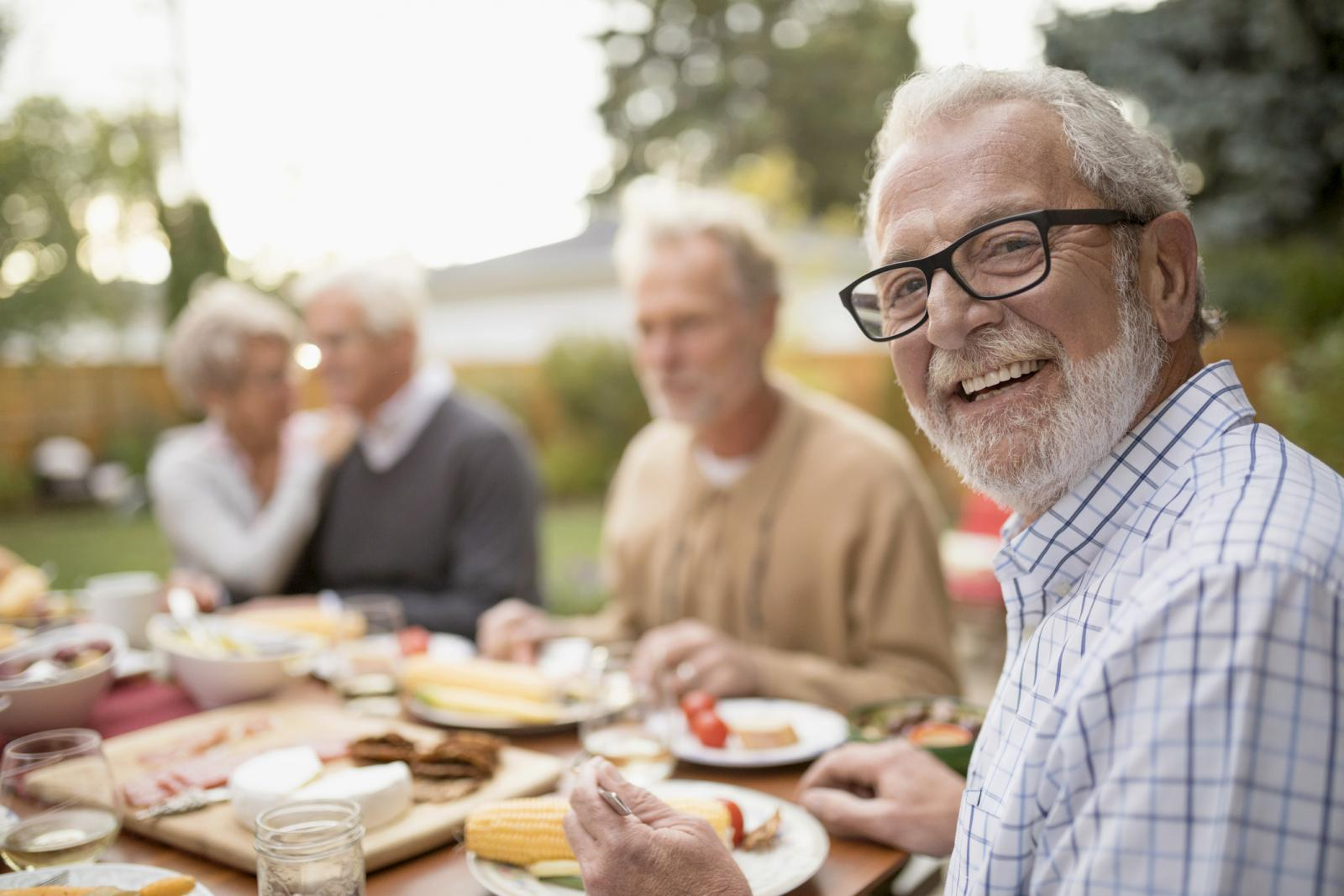 Smiling senior man enjoying garden party