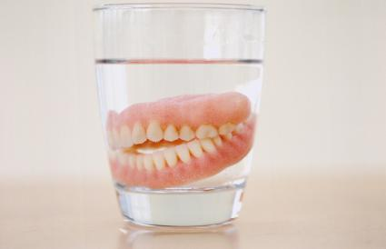set of dentures in a glass of water