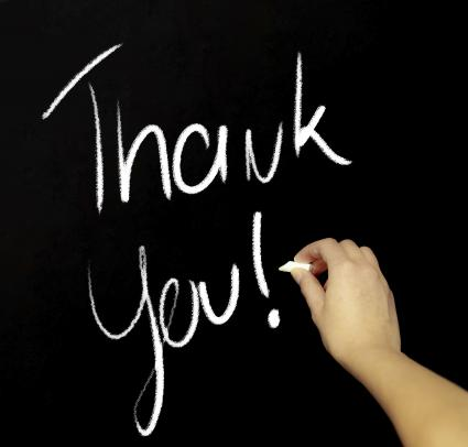 Hand writing thank you with chalk in black board