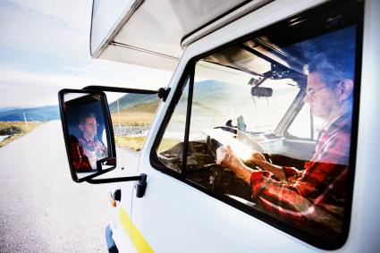 Senior man in camper van looking at map on road in mountains