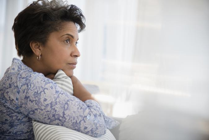 Woman clutching pillow looking pensive