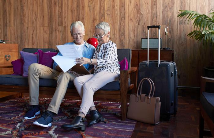 Mature couple looking through check-in clip board
